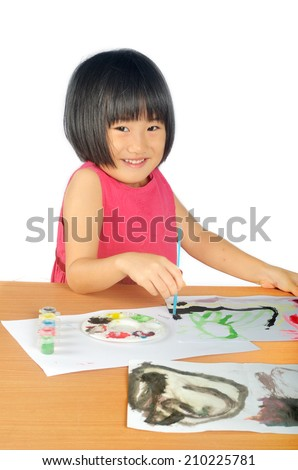 Asian little girl paints pictures with bright color brush - stock photo