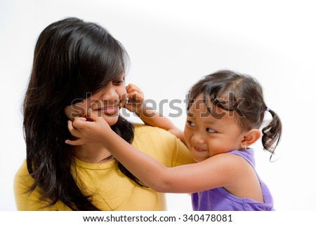 Asian Little Girl Pinch Teen Sister Cheek - stock photo