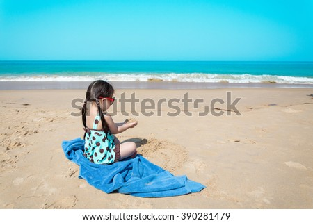 Asian little girl playing on sand beach - stock photo