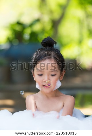 asian little girl playing with water and foam - stock photo