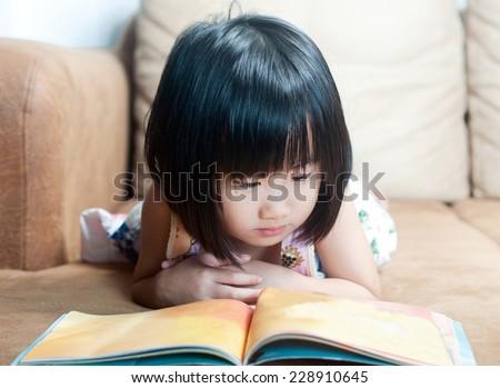 Asian little girl reading her book - stock photo