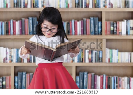 Asian little girl reads book seriously in library with bookcase background - stock photo