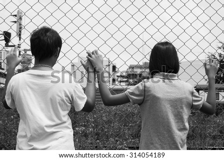 asian little girl sad hand hold jail at Railroad,railway station,black and white tone - stock photo