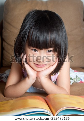 Asian little girl smiling while reading book  - stock photo
