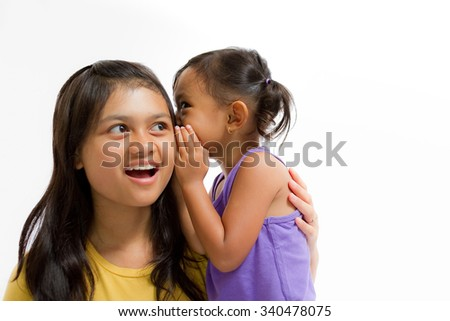 Asian Little Girl Whispering Secret Story to Teen Sister Isolated on White - stock photo