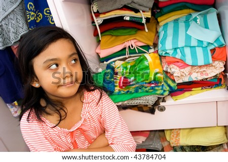 asian little girl with her clothes collection in the closet