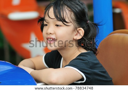 Asian little kid playing in the amusement park - stock photo