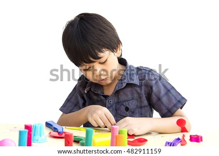 Asian lovely boy is playing clay happily over white background