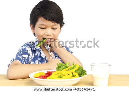 Asian lovely boy showing enjoy expression with fresh colorful vegetables and glass of milk isolated over white background