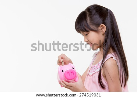 Asian lovely child putting coins into piggy bank - stock photo