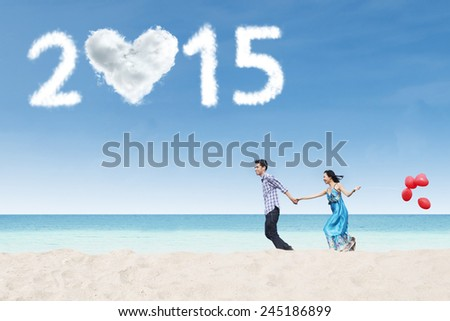 Asian lovers holding hands and run together on beach enjoy new year holiday - stock photo