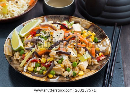 asian lunch - fried rice with tofu and vegetables on dark wooden table, close-up - stock photo