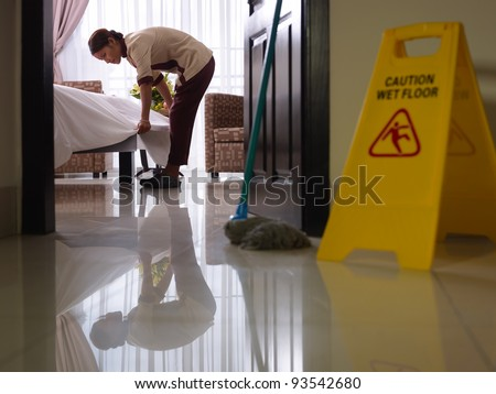 Asian maid tidying up bed and cleaning luxury hotel room - stock photo