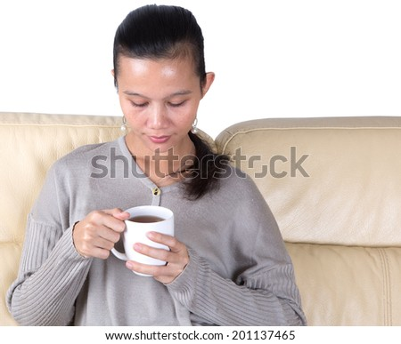 Asian Malay female relaxing on a sofa with a mug of hot drink