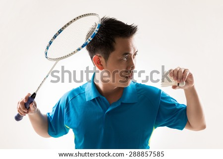 Asian male badminton player on white background.