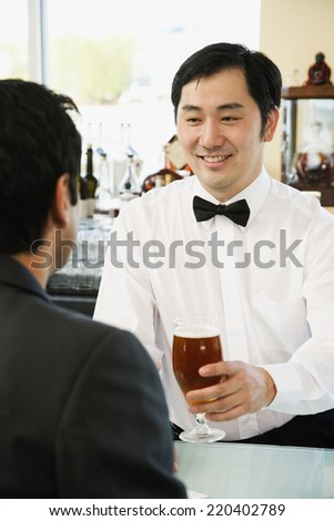Asian male bartender serving man drink at bar - stock photo
