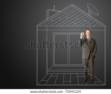 asian male businessman with marker in fictional house writting something on glass writeboard - stock photo