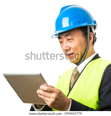 Asian male construction manager with a tablet - stock photo