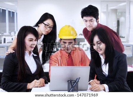 Asian male contractor is explaining his plan to team at workplace - stock photo