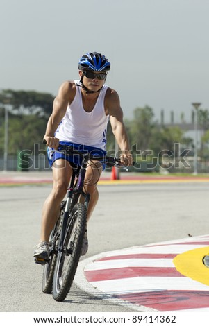 Asian male Cyclist training on a road - stock photo