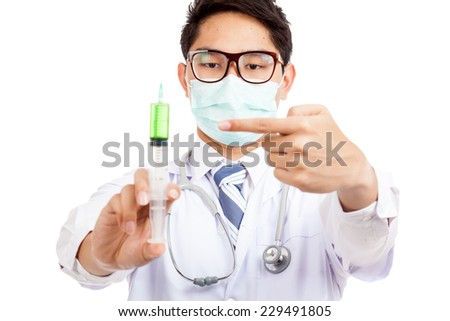 Asian male doctor wear mask point to syringe  isolated on white background - stock photo