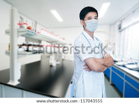 Asian male doctor with face mask portrait standing inside hospital building