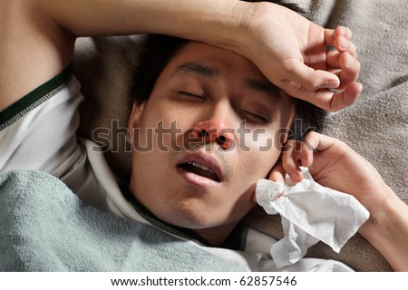 Asian male got a headache and flue, sleeping on bed - stock photo