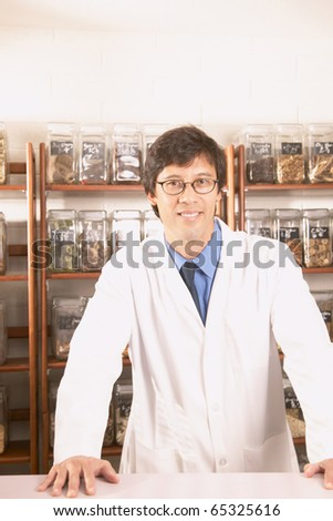 Asian male herbalist doctor in front of Chinese medicinal herbs - stock photo