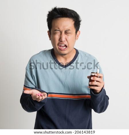Asian male holding medicine bottle while sneezing, on plain background - stock photo