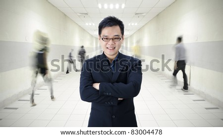 asian male in a tunnel with people walking in hurry - stock photo