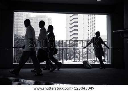 asian male senior citizen standing leaning on fence on bridge looking right, ignored by 3 male passed by pedestrians, 1 on phone, walking synchronize toward left. urban buildings city scene at back. - stock photo