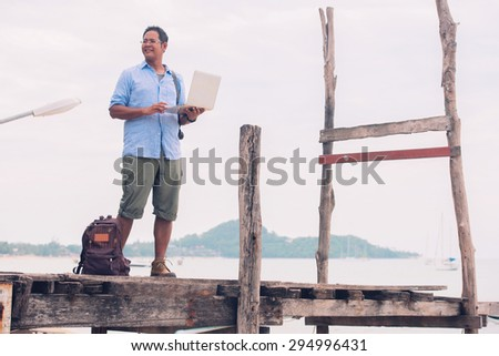 Asian male tourist standing at old wooden bridge using computer