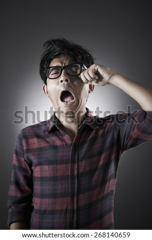 Asian male wearing glasses in low key with sleepy pose - stock photo