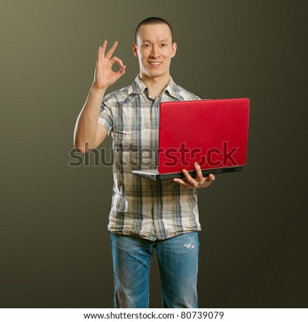 asian male with laptop in his hands shows OK, looking on camera