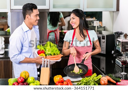 Asian man and woman cooking together in kitchen preparing dinner - stock photo