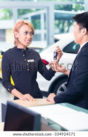 Asian man at car rental receiving key