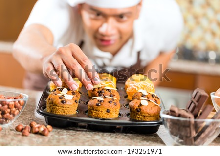 Asian man baking homemade cup cake muffins in his kitchen for dessert - stock photo