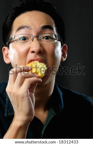 Asian man chomping down a piece of bread - stock photo