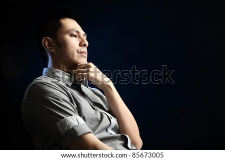 Asian man contemplating over black background