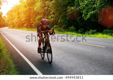 Asian man cycling on the road at morning sunrise with lens flare