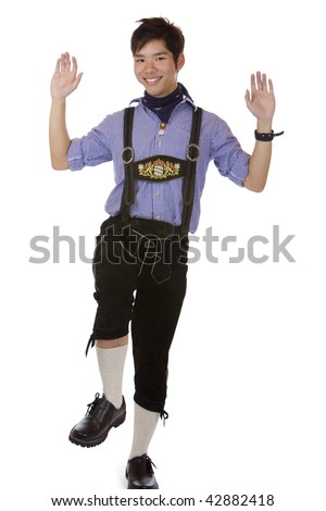 """Asian man dressed in Oktoberfest leather trousers (Lederhose) is doing the traditional Bavarian dance called """"Plattln"""". Isolated on white. - stock photo"""