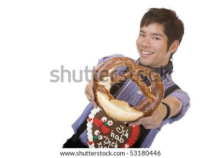 Asian man dressed with Bavarian Lederhose holds an Oktoberfest pretzel in camera. Isolated on white. - stock photo