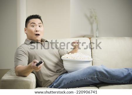 Asian man eating popcorn on sofa with remote control - stock photo