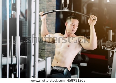 Asian man exercising at the gym on a machine in fitness - stock photo