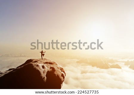 Asian man, fighter practices martial arts in high mountains above clouds at sunset. Kung fu and karate pose. Also concepts of discipline, concentration, meditaion etc. Unique - stock photo