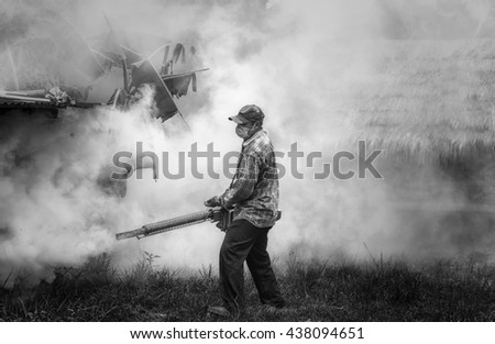 Asian man fogging mosquitoes,black and white - stock photo