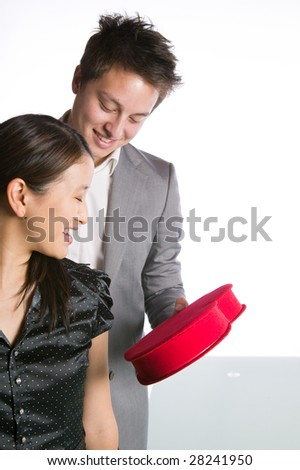 Asian man giving his partner a valentines box of chocolates - stock photo