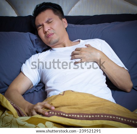 asian man has a heart attack symptoms on bed in the night - stock photo