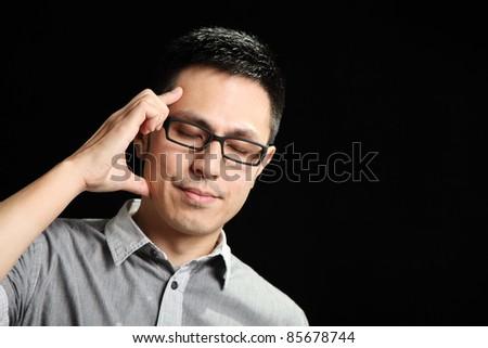 Asian man having a headache over black background - stock photo