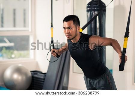Asian man having fitness TRX training at gym - stock photo
